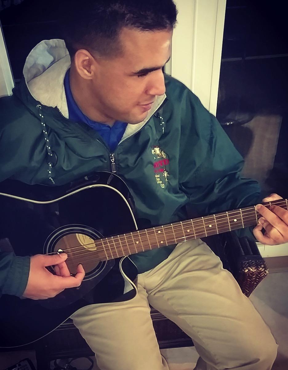 Photo of Logan Merrill playing an acoustic guitar in a hair salon